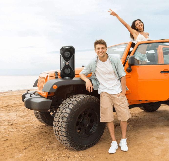 At the beach young couple enjoying music in the jeep