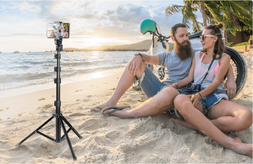 Men and women sitting on the beach and taking selfie with the help of tripod